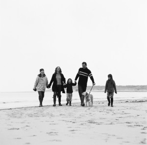 Couple Walking on the Beach with Their Three Daughters and Dog