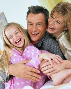 Happy Family Laughing in Bed