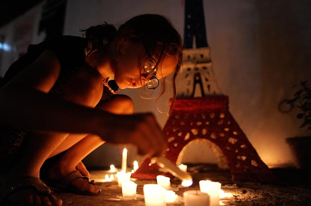 MANILA, PHILIPPINES - NOVEMBER 16:  A young girl lights candles to honour victims of the Paris terror attacks at Alliance Francais Manila on November 16, 2015 in Manila, Philippines. 129 people were killed and hundreds more injured in Paris following a series of terrorist acts in the French capital on Friday night.  (Photo by Dondi Tawatao/Getty Images) *** BESTPIX ***
